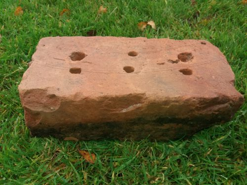 Cored brick displaying lifting tool marks.